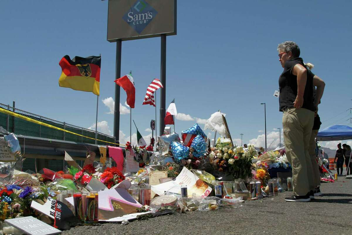 In this Aug. 12, 2019 photo, mourners visit the makeshift memorial near the Walmart in El Paso, Texas, where 23 people were killed in a mass shooting.