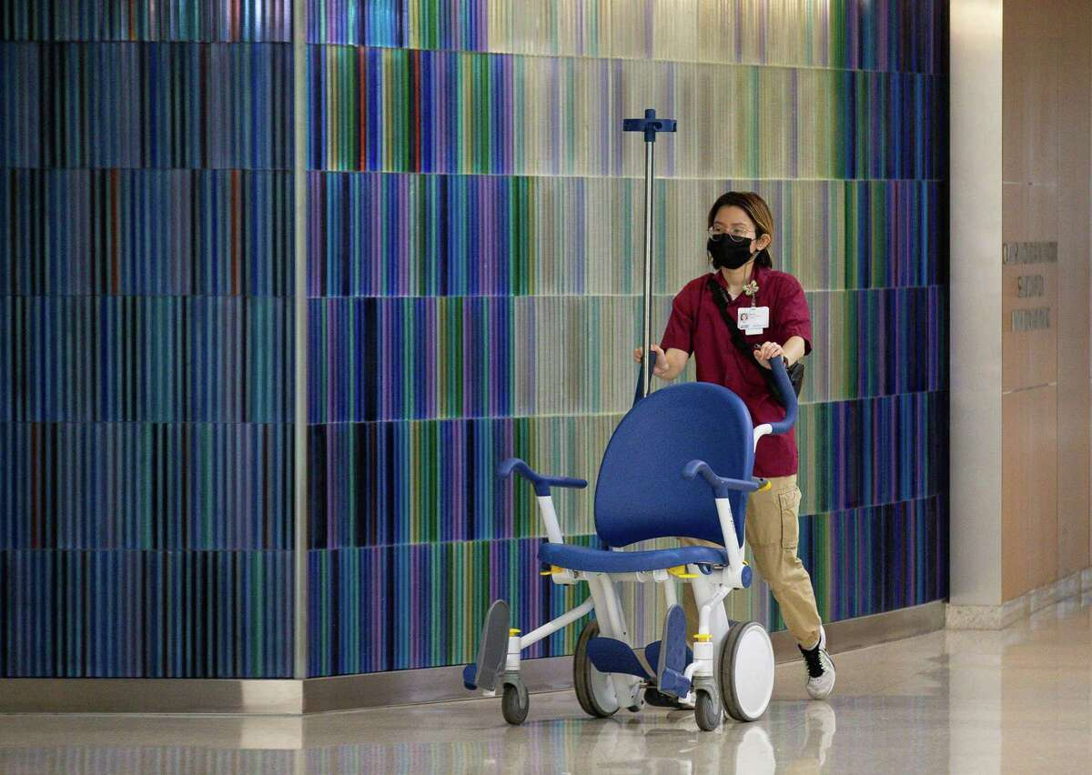 Medical professionals walk through one of the hallways at Houston Methodist Hospital on Monday, Aug. 2, 2021, in Houston.
