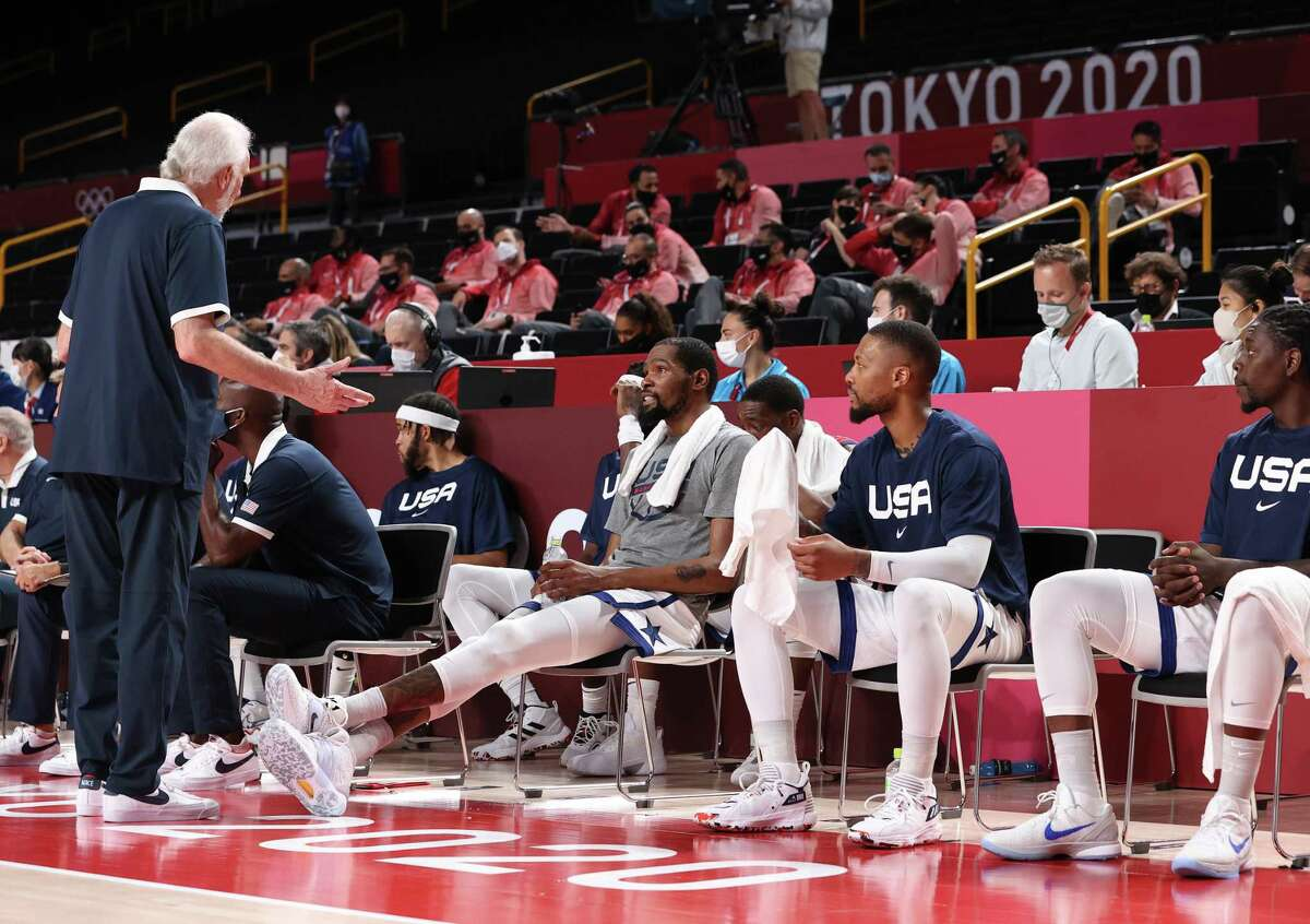 U.S. coach Gregg Popovich speaks to Kevin Durant and Damian Lillard on the bench during the second half against Team Australia at Saitama Super Arena on August 5, 2021.