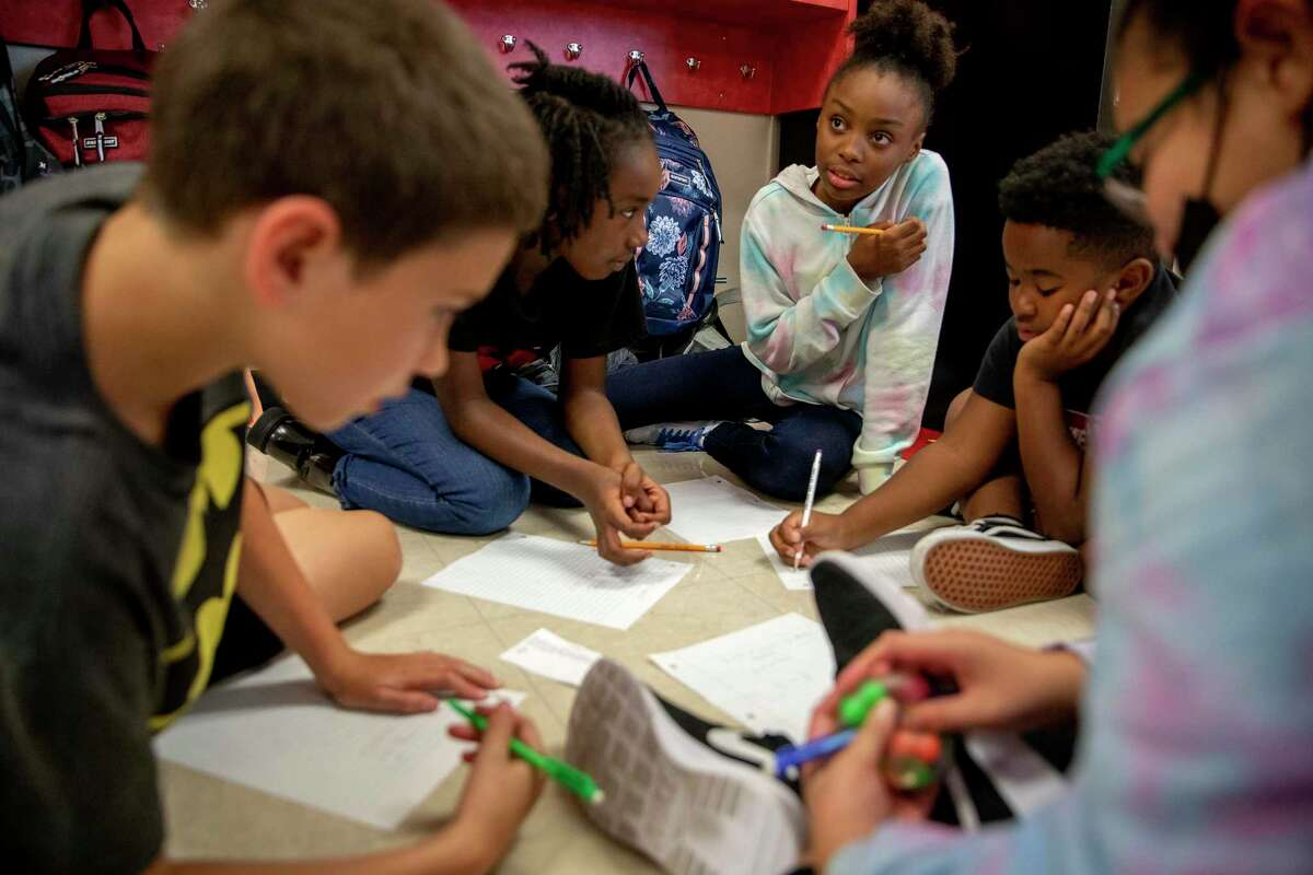 Converse Elementary fifth grader, Jayme Cunningham, (center) helps her classmates, Jaden Hill, Ariyanna Adams, Michael Wright and Chloe Mora solve a word problem. The Judson ISD school switched to a year-round calendar to counter the learning loss aggravated by the pandemic - and now is among the first to open for the fall as schools lose their ability to reduce risk factors for new infections.