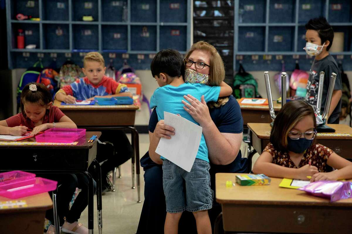 John James Cardenas, a second grader at Converse Elementary, hugs his principal, Cynthia Davis. The Judson ISD school switched to a year-round calendar to counter the learning loss aggravated by the pandemic - and now is among the first to open for the fall as schools lose their ability to reduce risk factors for new infections.