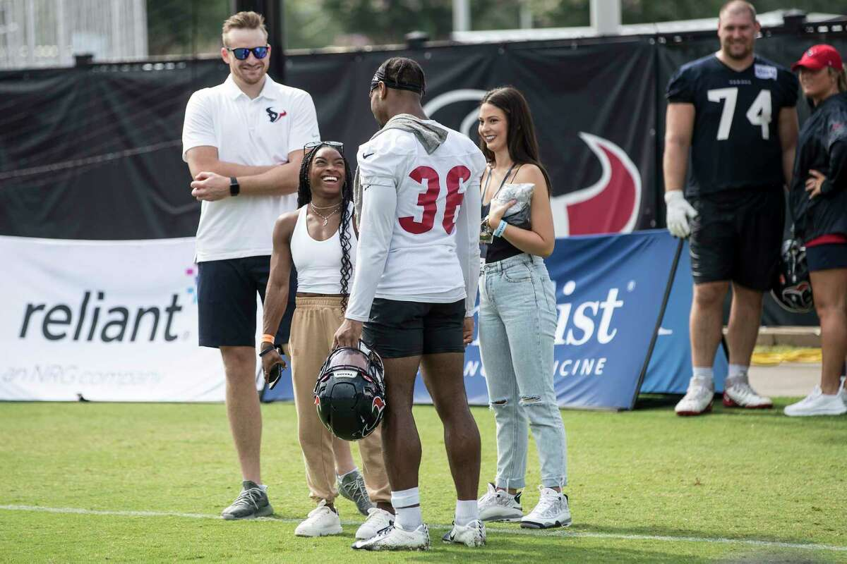 Olympic gymnast Simone Biles stands on the field and talks to her boyfriend Houston Texans defensive back Jonathan Owens (36) as she takes in Texans training camp football practice Friday, Aug. 6, 2021, in Houston.