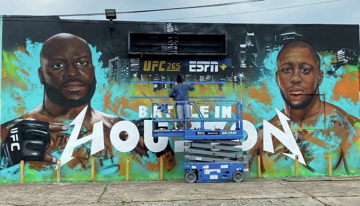 Houston artist Franky Cardona works on a mural Thursday, Aug. 5, 2021, promoting UFC 265's main event between Derrick Lewis and Ciryl Gane. The mural is located at 2102 Leeland Street.
