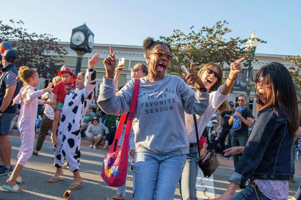 Michele Callwood (center) dances with her longtime friends Michelle Jeffers (right) and Moy Chiu (far right) during Novato's Rock the Block street party. News of a new housing development at the nearby Fireman's Fund campus could spur more activity in the Marin County city.