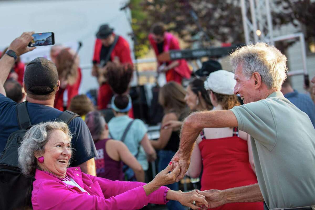 Cari Pace (left) and Bob Koch dance together while the Pop Rocks dance band performs on stage during Novato's Rock the Block street party.