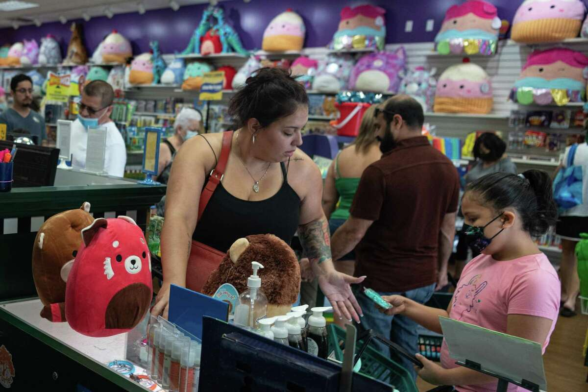 Bianca Ramirez and her daughter Isabella, 8, pay for the Squishmallows they recently bought the Learning Express store in the Alamo Quarry Market.