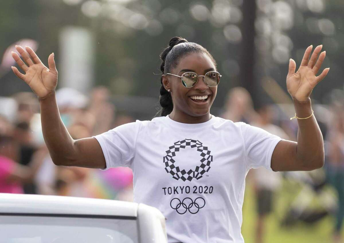 Simon Biles waves at supporters after she comes home from the 2020 Tokyo Olympics during a welcome home parade for Simon Biles in her neighborhood of Benders Landing, Thursday, Aug. 5, 2021, in Spring. Biles is returning to Houston after winning two Olympic medals at the 2020 Tokyo Olympics.