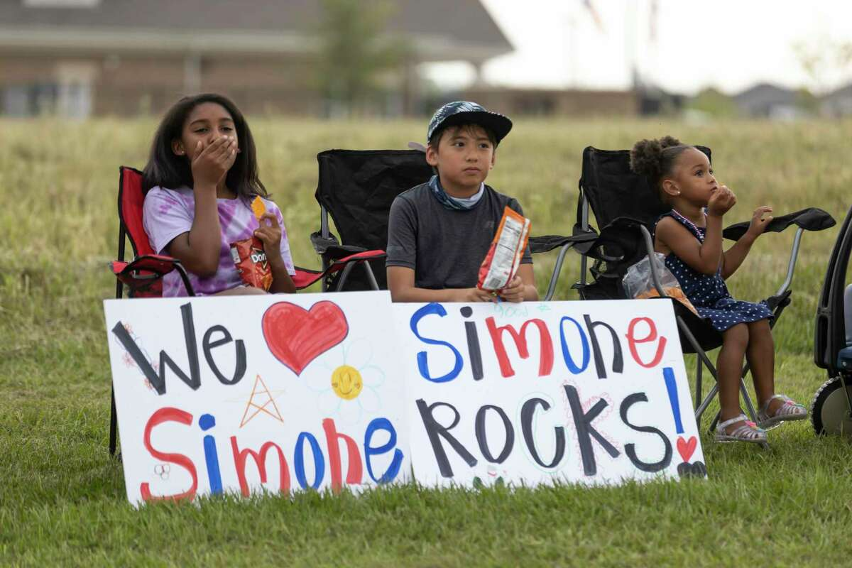 Supporters sit on the curb as they await Simone Biles arrival during a welcome home parade for Biles in her neighborhood of Benders Landing, Thursday, Aug. 5, 2021, in Spring. Biles is returning to Houston after winning two Olympic medals at the 2020 Tokyo Olympics.