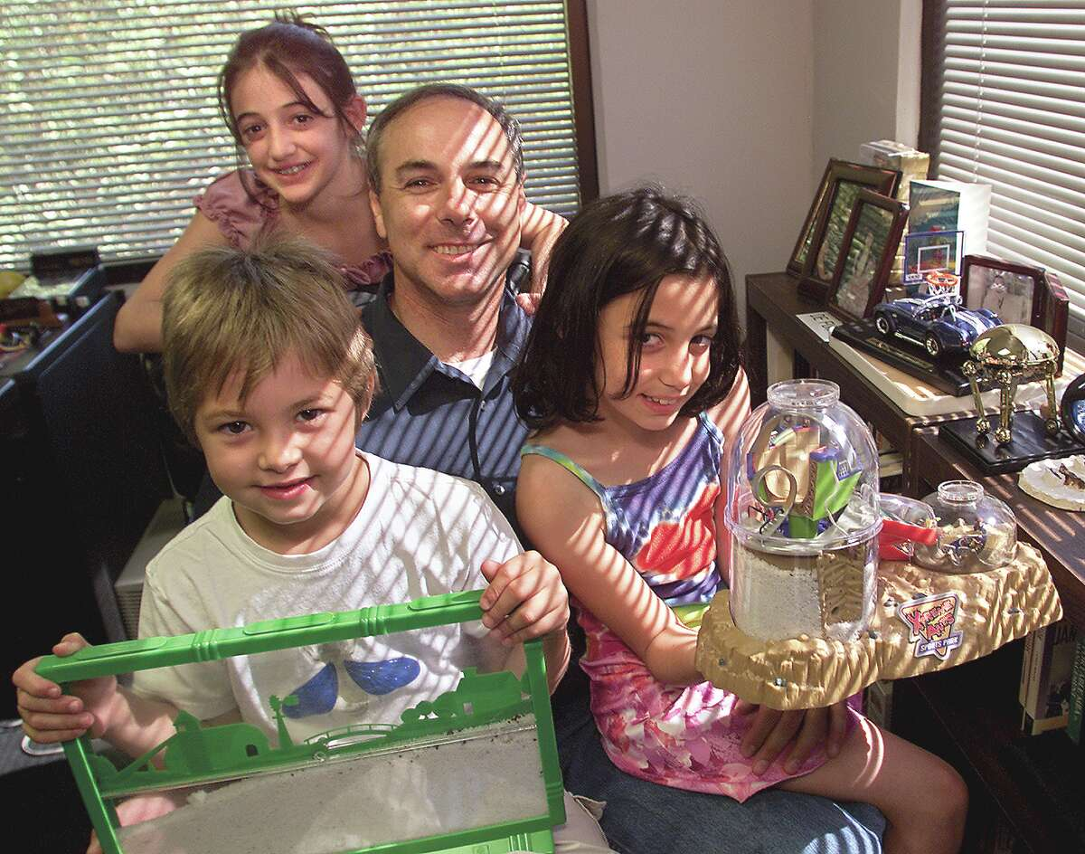 Steven Levine, president of Uncle Milton Industries, an ant farm company sits at his office surrounded by his children displaying different versions of ant farms.