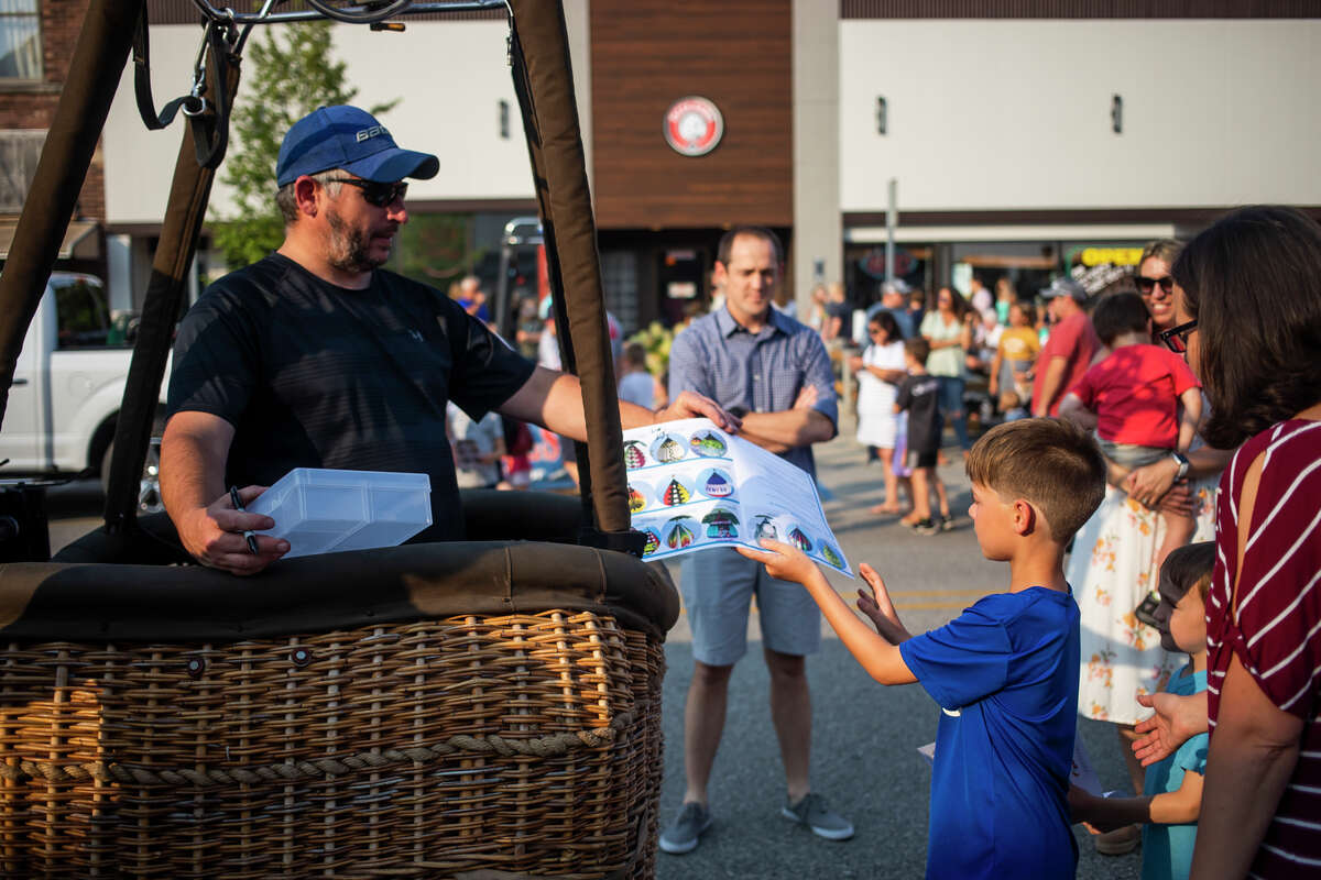 Hot air balloon pilot Scott King, left, signs his autograph for EJ Watt, 8, right, during the Main Street Glow event as part of the River Days Festival Thursday, Aug. 5, 2021 in downtown Midland. (Katy Kildee/kkildee@mdn.net)