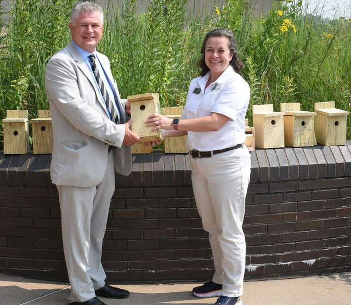 Madison County Regional Superintendent Robert Werden, left recently presented Lori Belkamp, Superintendent of the Cahokia Mounds State Historic Site, with bird and bat houses made by Madison County students at the Regional Office of Education Summer Construction Camp.