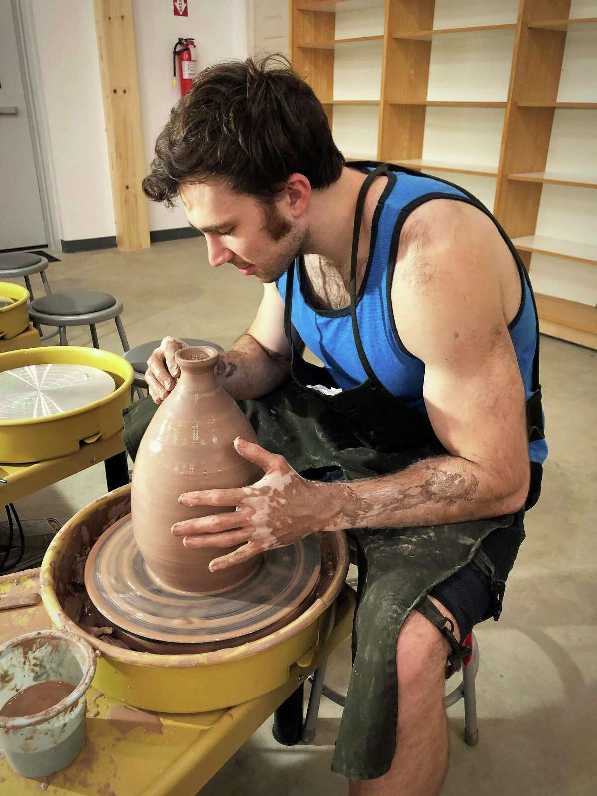 Co-owner Jesse Lane gets his hands dirty as he works on his project at the ceramics wheel in his and his wife's new studio in Magnolia.
