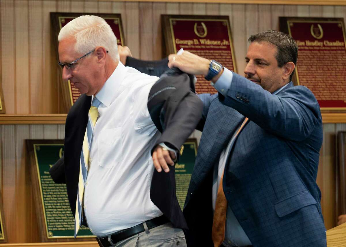 Owner Mike Repole helps inductee trainer Todd Pletcher with his Hall of Fame jacket during the Hall of Fame inductions at the Fasig Tipton Sales Pavilion on Friday, Aug. 6, 2021, in Saratoga Springs, N.Y.