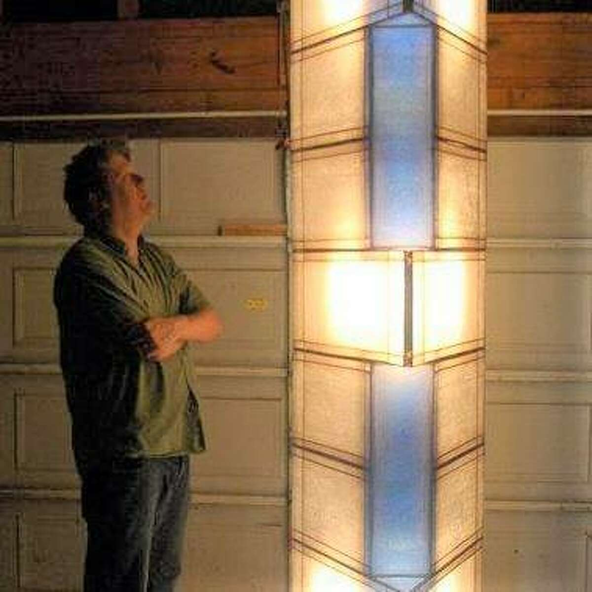 St. Louis artist Bob Hartzell gazes at one of his light sculpture pieces. His solo exhibit Satellites: The Forgotten Works of Bob Hartzell opens Saturday at Good Weather Gallery, Edwardsville.