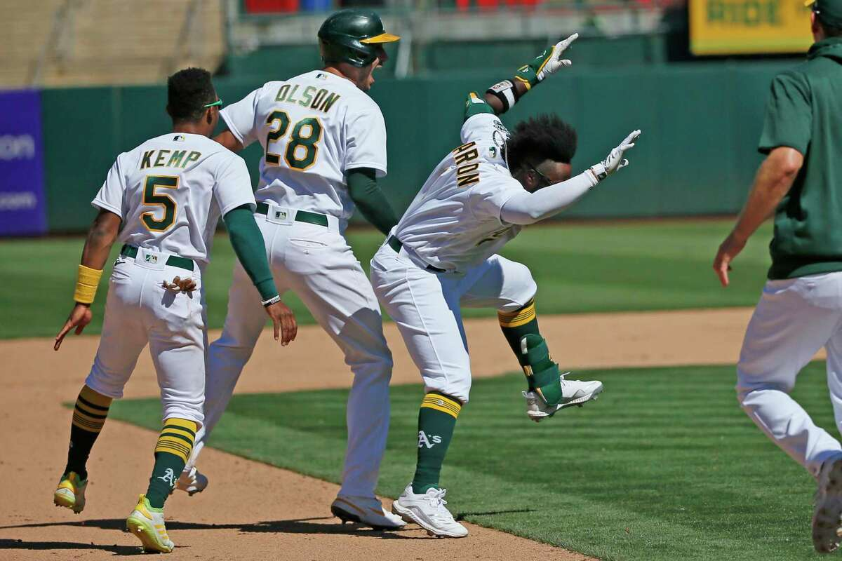 Oakland Athletics Matt Olson (28) celebrates his walk-off double with the A's Josh Harrison (1) and Tony Kemp (5) as they win the MLB game against the San Diego Padres in the tenth inning at RingCentral Coliseum on Wednesday, Aug. 4, 2021, in Oakland, Calif. The Athletics won 5-4.