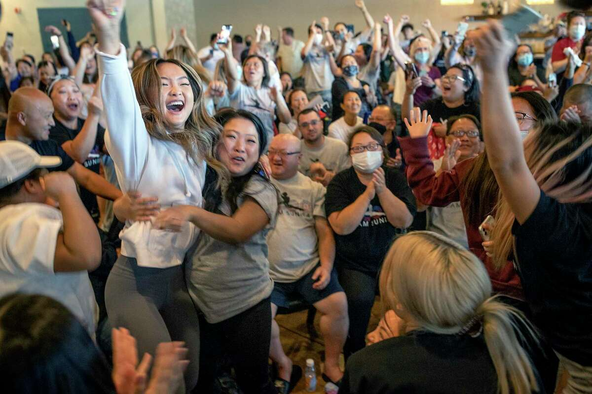 Shyenne Lee, 18, left, older sister of Olympian Sunisa Lee, reacts alongside family and friends watching from Oakdale, Minn., as she clinches the gold July 29.