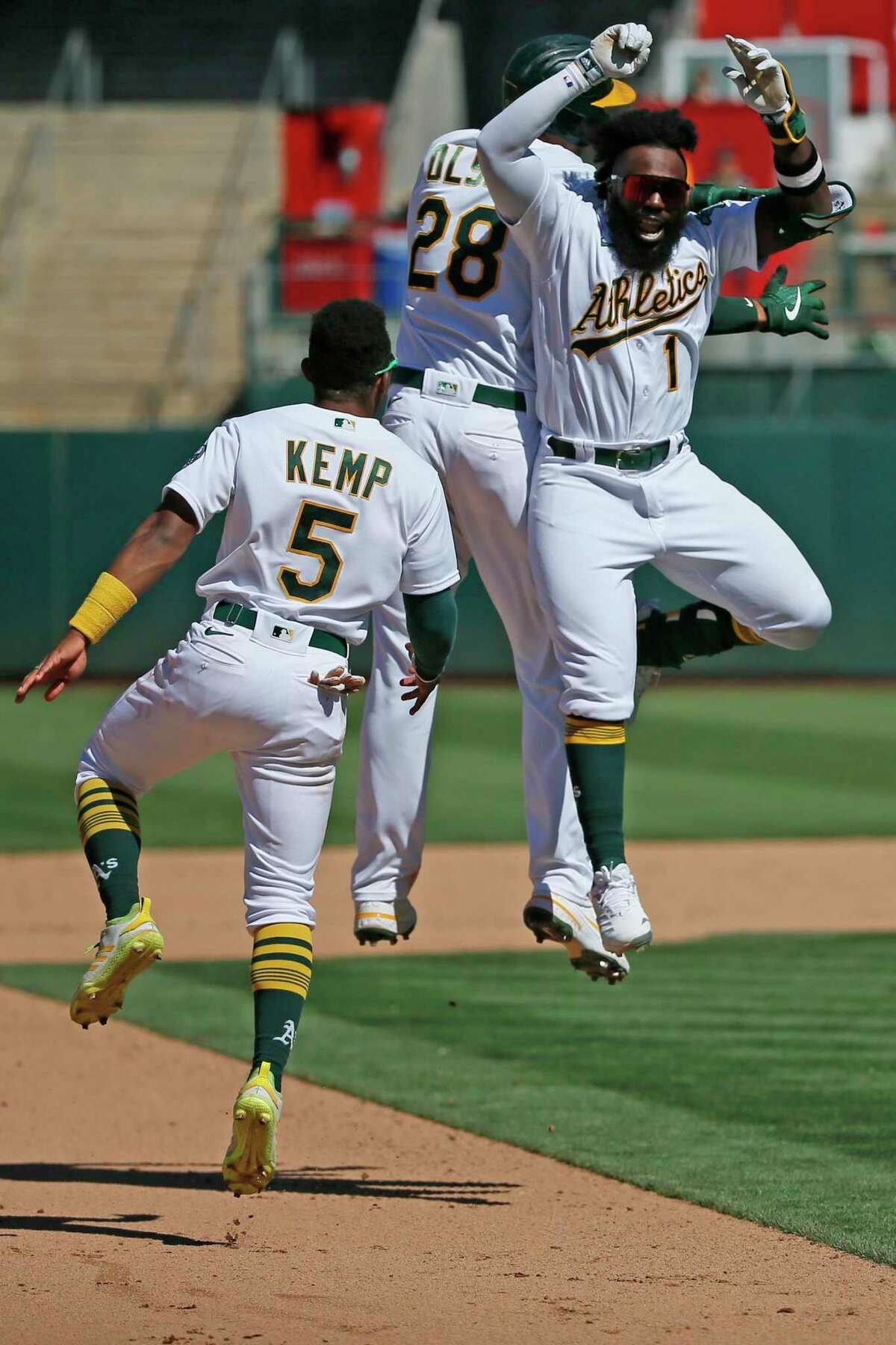 Oakland Athletics Matt Olson (28) celebrates his walk-off hit with the A's Josh Harrison (1) and Tony Kemp (5) to win the MLB game against the San Diego Padres in the tenth inning at RingCentral Coliseum on Wednesday, Aug. 4, 2021, in Oakland, Calif. The Athletics won 5-4.