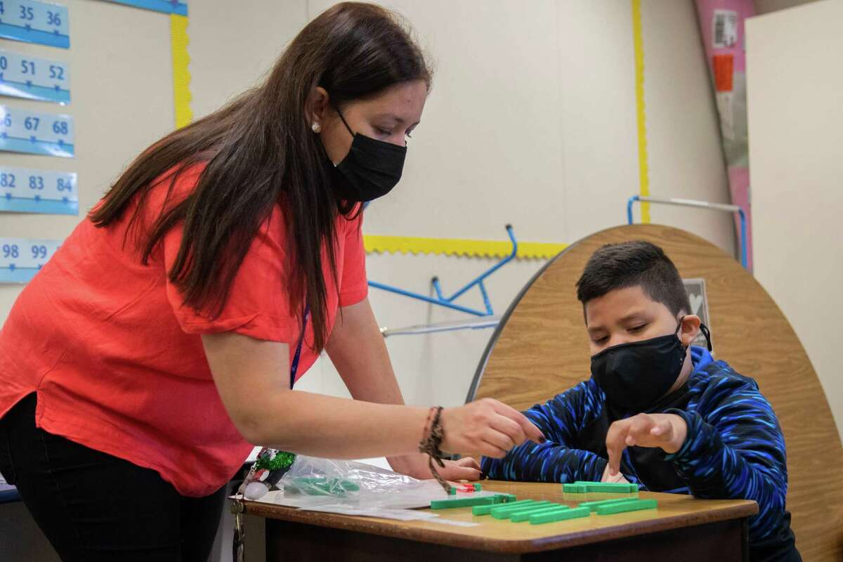 Alief ISD's Best Elementary School math interventionist teacher Mayra Medina works with second-grader Orlando Bravo to review math exercises April 8.