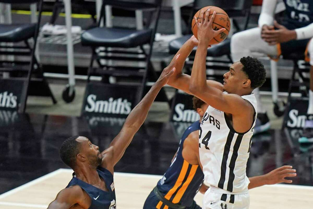 Spurs' Devin Vassell (24) shoots as the Utah Jazz's Kyle Fogg, left, defends during the first half of an NBA summer league basketball game Wednesday, Aug. 4, 2021, in Salt Lake City.