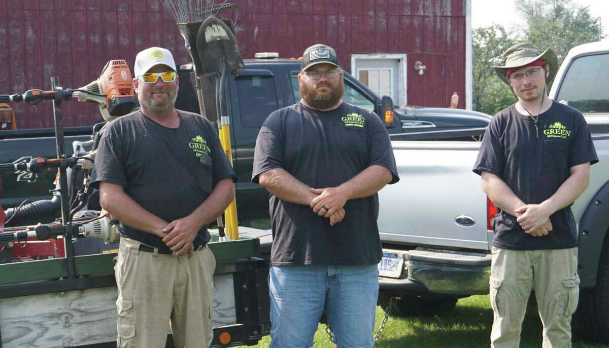 From left-to-right: Simply Greenowner Jeff Jackson, Brian Sutton and Ian Norris pose in front of one of their work trucks. Not pictured in photo: Shawn Bertle, Josh Tait and Mike Barton.