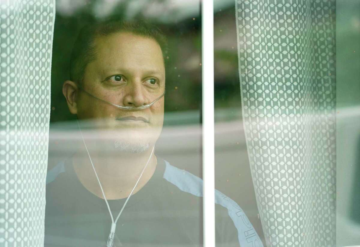 Andres Perekalski looks through the window of his home Thursday, Aug. 5, 2021 in Cypress, where he is quarantined from COVID-19. He spent two weeks in a COVID ICU. He regrets not being vaccinated and wants others to learn from his mistake.