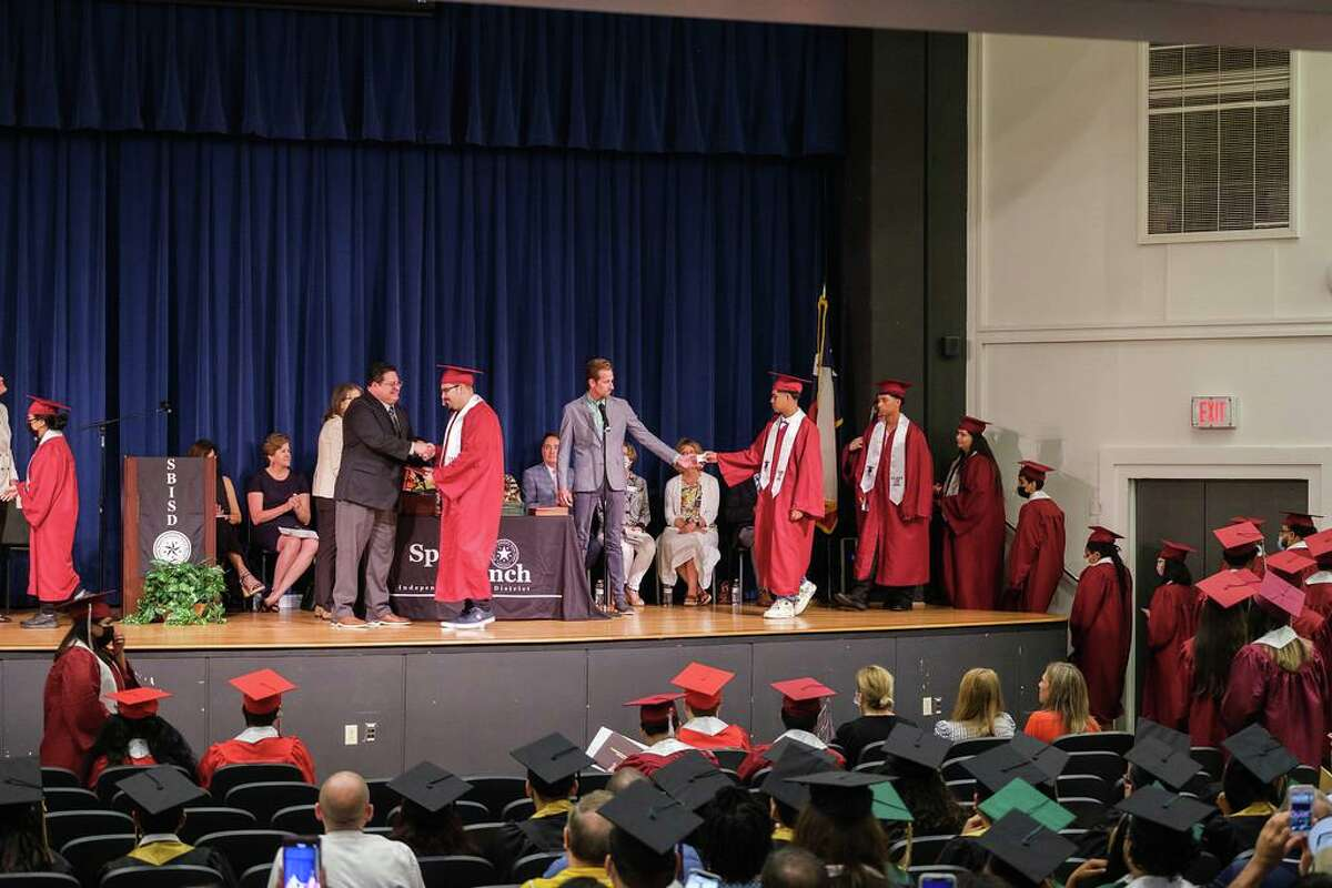 Northbrook graduates cross the stage to receive their diplomas from principal Antonio Avalos during the Spring Branch ISD summer graduation ceremony at the Spring Branch Education Center on Aug. 5.
