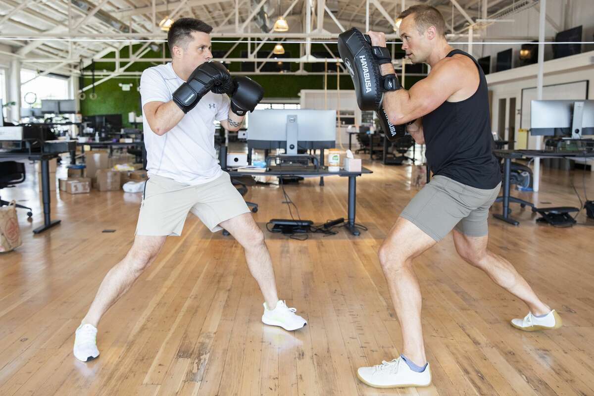 Phil McDougall (right), wellness director at the company Fast, spars with Domm Holland in a training session at the Fast office in San Francisco.