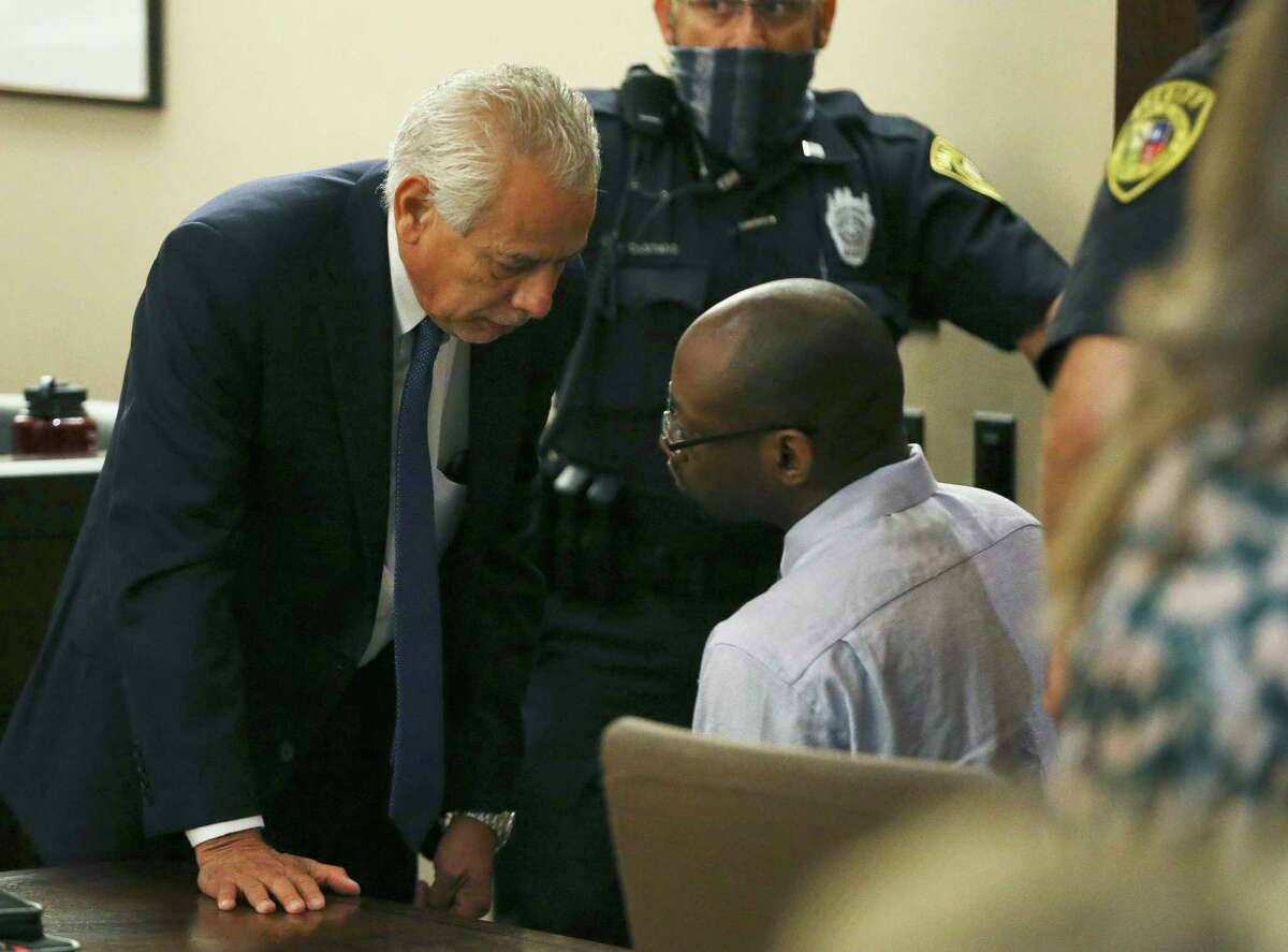 Defense attorney Joel Perez talks with his client Otis McKane after both the state and the defense complete their closing arguments in his capital murder trial Friday.