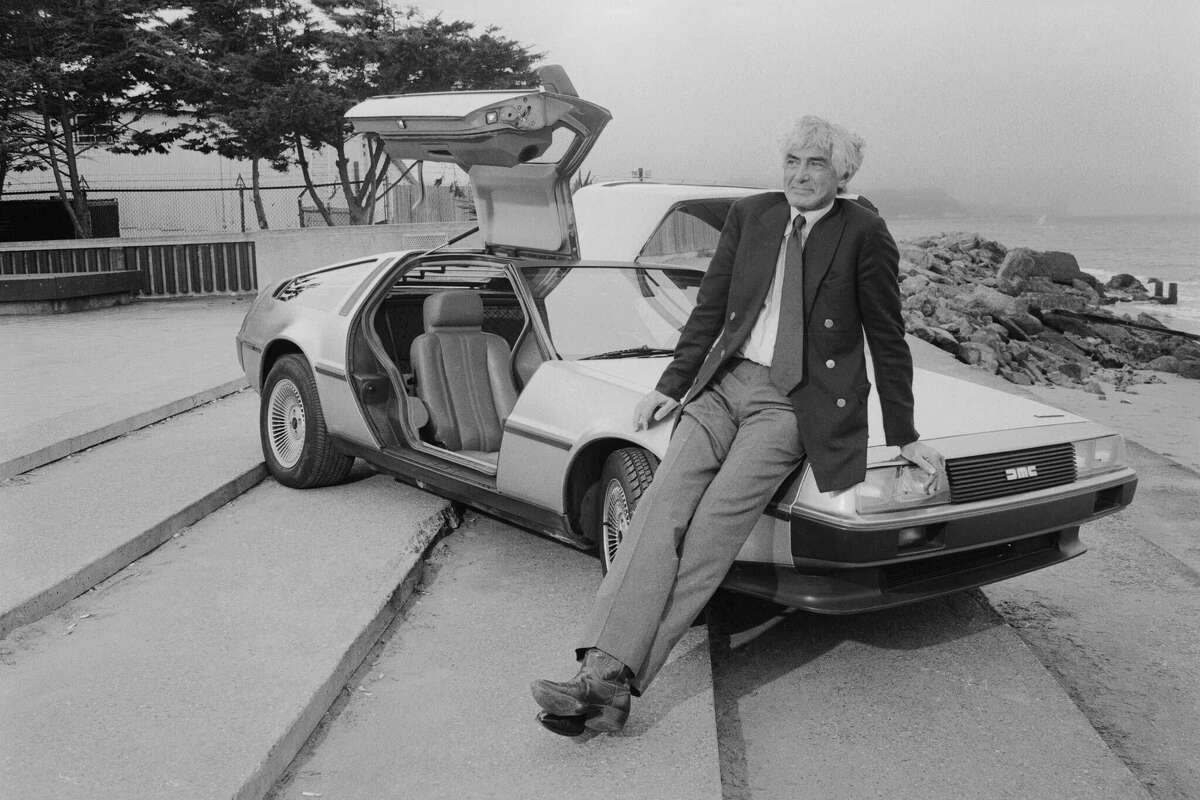 Automobile entrepreneur John DeLorean poses with one of his distinctive sports cars at a beach next to San Francisco Bay.