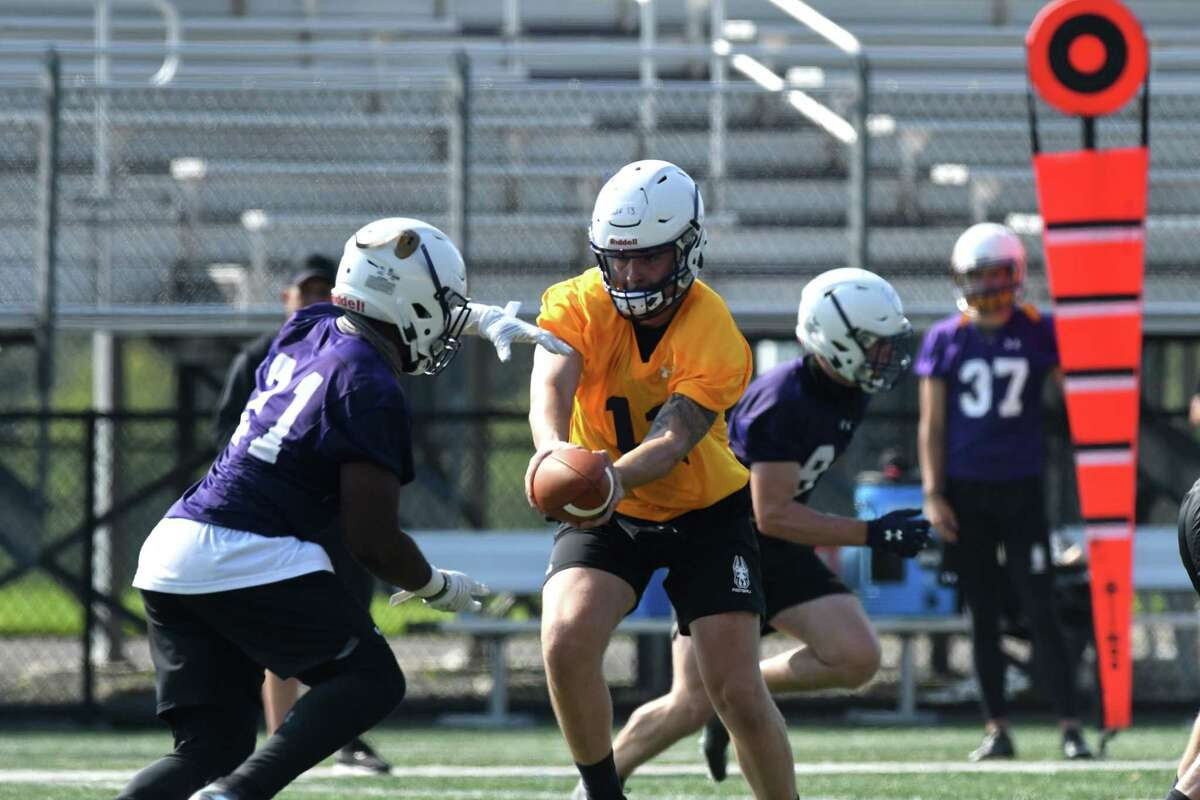 University at Albany quarterback Jeff Undercuffler makes a handoff to running back Karl Mofor ,left, during the first practice of the season on Friday, Aug. 6, 2021, at Tom and Mary Casey Stadium in Albany N.Y. The teams?• first home game takes place Saturday September 11 against Rhode Island. They face North Dakota State on the road on September 4.