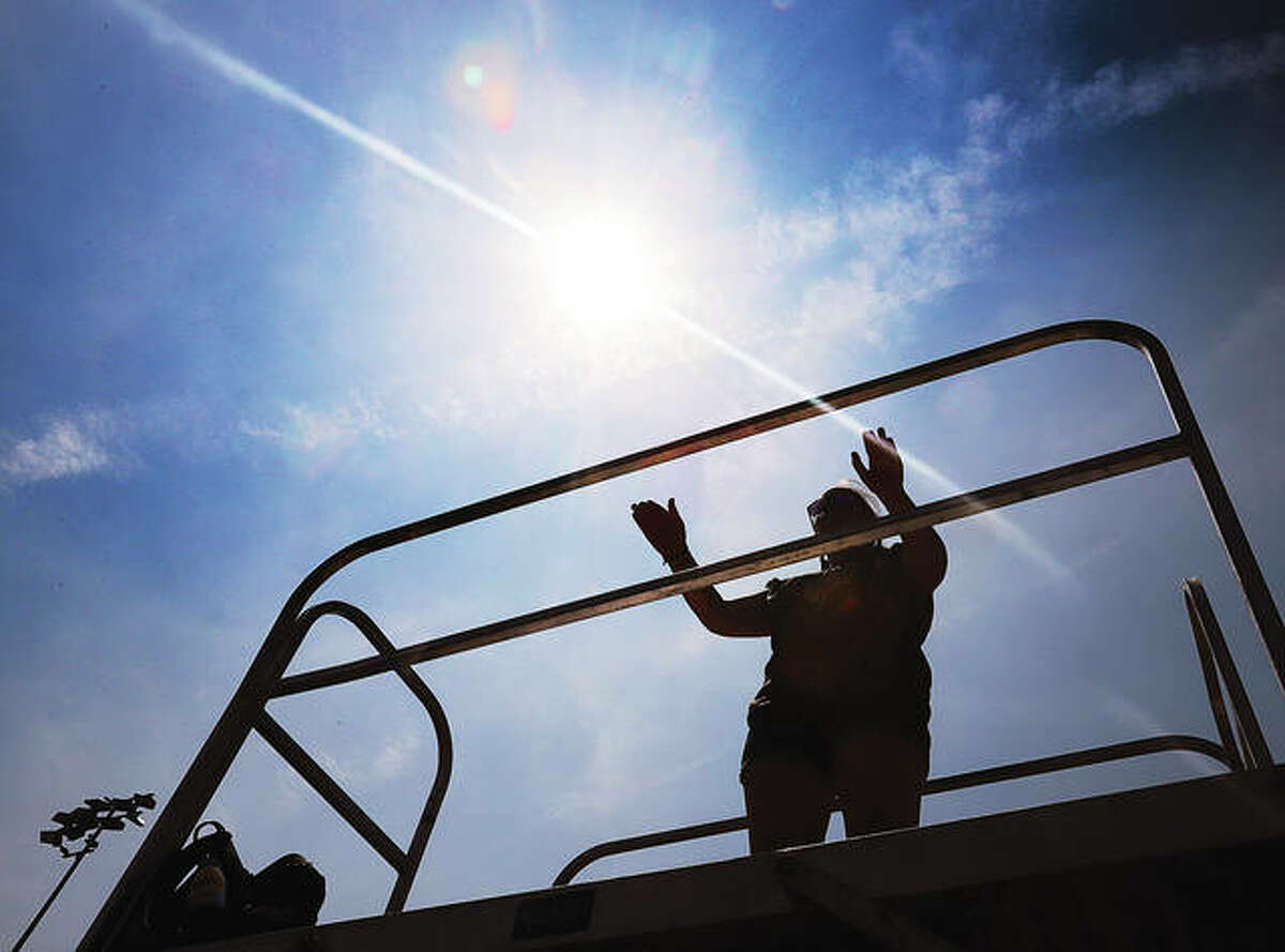 Meredith Rulo, a drum major for the band, is silhouetted as she directs students from a platform set up on the track at Public School Stadium during the past two weeks' band camp. - John Badman The Telegraph