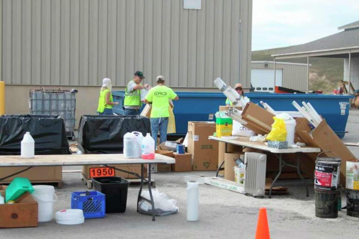 Workers assist people in collecting materials during the annual Household Hazardous Waste collection at the Manistee County Road Commission garage in 2018. Volunteers are being requested for this year's event. (File photo)