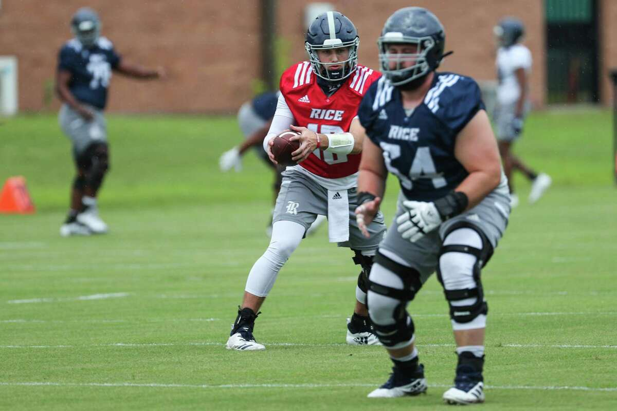 Rice quarterback Luke McCaffrey (12) takes a snap and rolls out behind offensive lineman Isaac Klarkowki (54) during practice Friday, Aug. 6, 2021, in Houston.