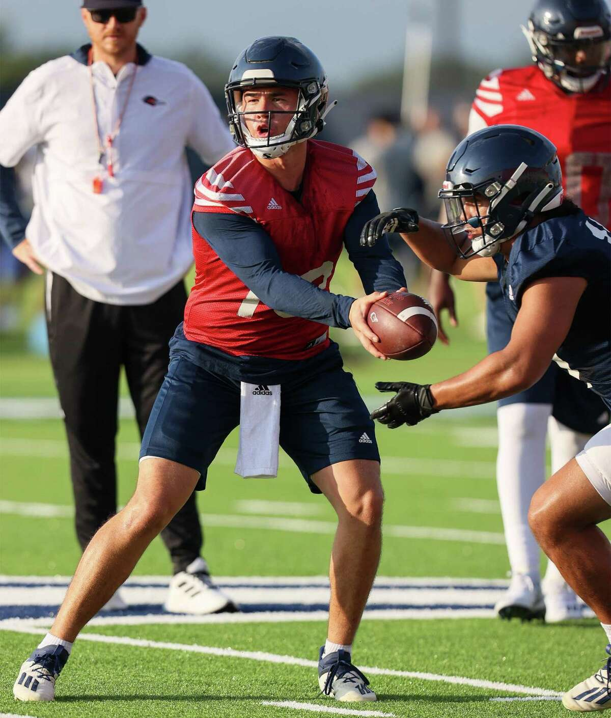 UTSA quarterback Josh Adkins prepares to hand off to running back Kaedric Cobbs during their first football practice of fall camp at the practice fields of the RACE facility on campus on Friday, Aug. 6, 2021.