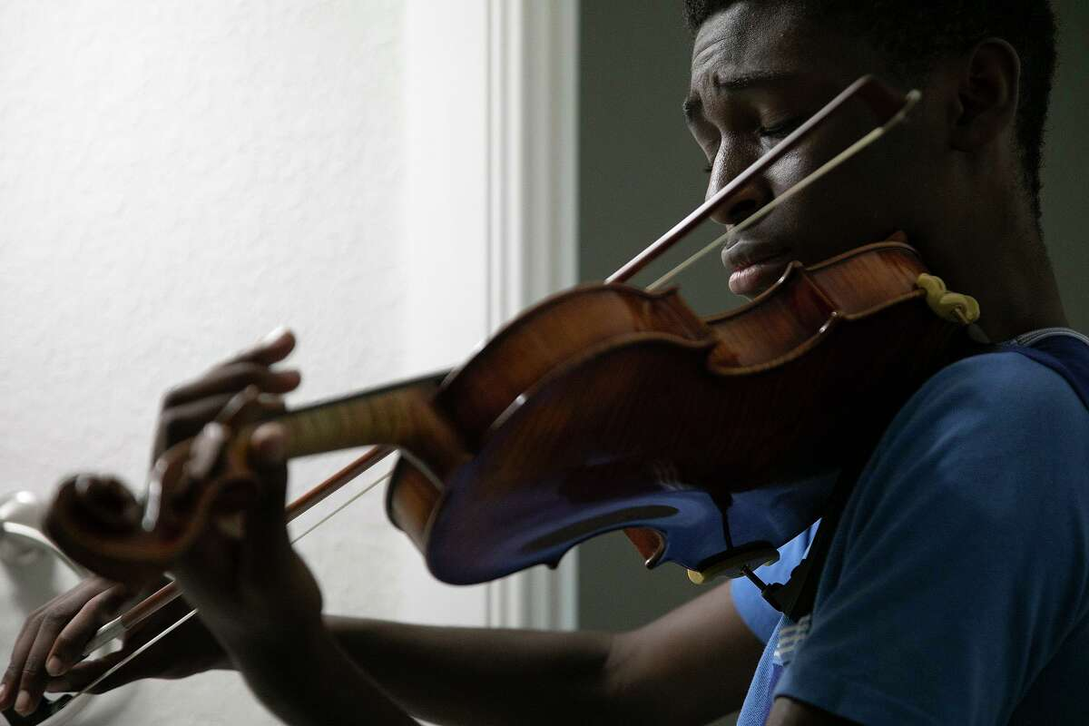 Samuel Igbo, 15, practices in a bathroom, where the acoustics are better than other rooms, at his home in Boerne. He is already practicing for his next audition this fall for Carnegie Hall's National Youth Orchestra.