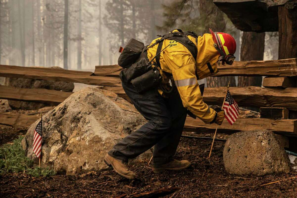 Captain AJ Alcocer of the Santa Rosa Fire Department adjusts a U.S. flag from the ground during the Dixie Fire in Lake Almanor West, California Thursday, Aug. 5, 2021.