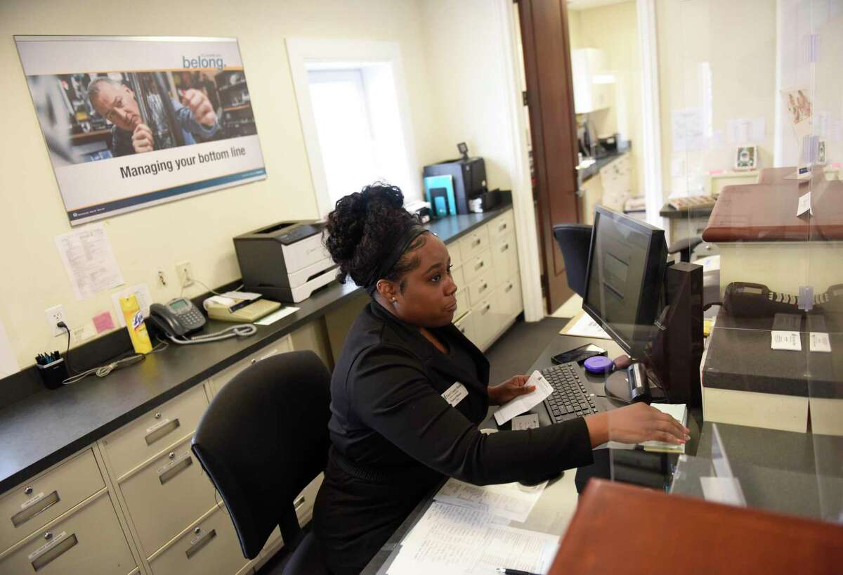 Bank teller Taishara Blanco assists a customer at the First County Bank branch at 2950 Summer St., in Stamford, Conn., on Thursday, July 8, 2021. First County Bank has recommended, but not required, that its employees get vaccinated against COVID-19.