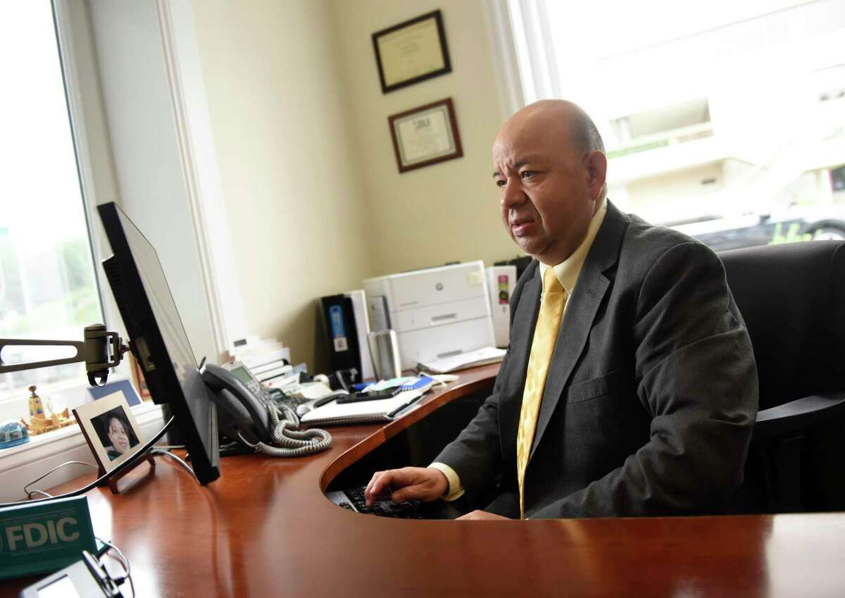 Branch Manager Camilo Duque Jr. works in his office at the First County Bank branch at 2950 Summer St., in Stamford, Conn., on Thursday, July 8, 2021. First County Bank has recommended, but not required, that its employees get vaccinated against COVID-19.