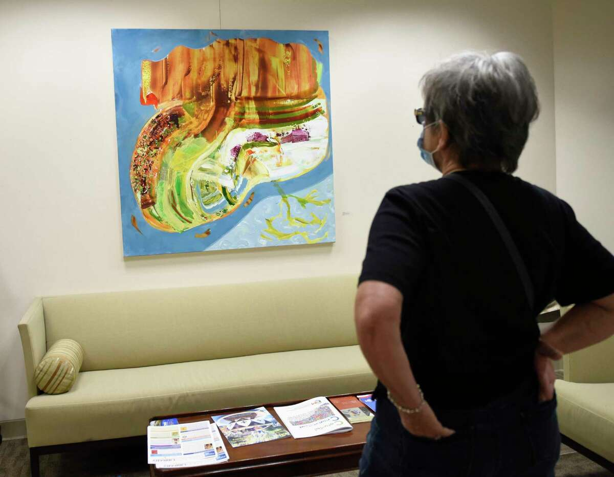 """Gallery curator Lina Morielli looks at Jay Petrow's painting """"Tropic of Cancer"""" at the Mayor's Gallery in the 10th floor of Stamford Government Center in Stamford, Conn. Thursday, Aug. 5, 2021. Petrow's work has been on display since before the COVID outbreak in March of 2020. His exhibition will finally hold its reception on Sept. 8 and be taken down soon after to make room for a new artist. The Mayor's Gallery typically rotates exhibits every two months, but COVID has forced the current exhibit to remain in place for the last 18 months."""