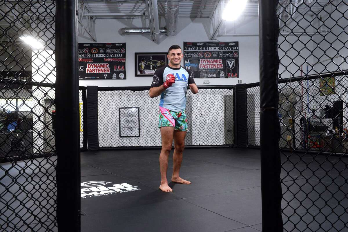 Nick Newell, a mixed martial arts fighter and a Milford native, poses in the cage at Fighting Art Academy CT, in Milford, Conn. Aug. 6, 2021. Notorious Nick, a feature film based on Newell's life, is now in theaters.
