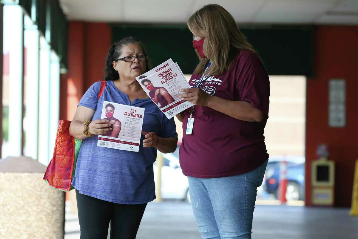 San Antonio Metropolitan Health District worker Mikela Villarreal, right, gives Marta Muñoz information about upcoming free COVID-19 vaccination events as district personnel worked the area around Las Palmas Shopping Center on Friday.
