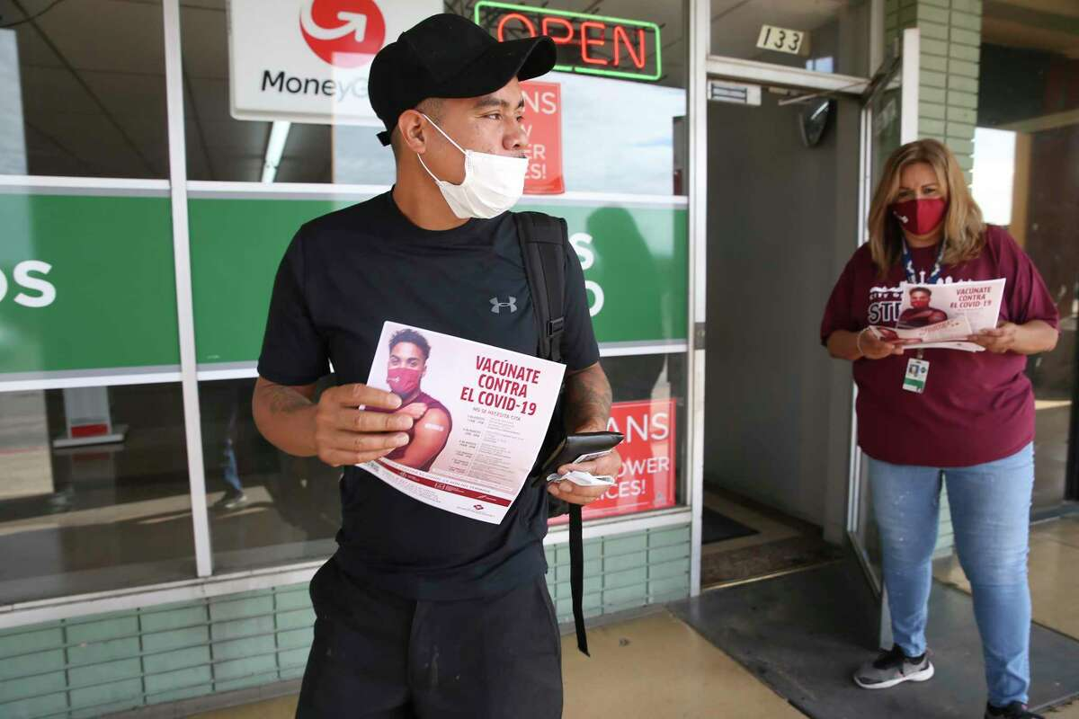 Jose Medina, left, receives information on upcoming free COVID-19 events from San Antonio Metropolitan Health District worker Mikela Villarreal at Las Palmas Shopping Center on the city's West Side on Friday.