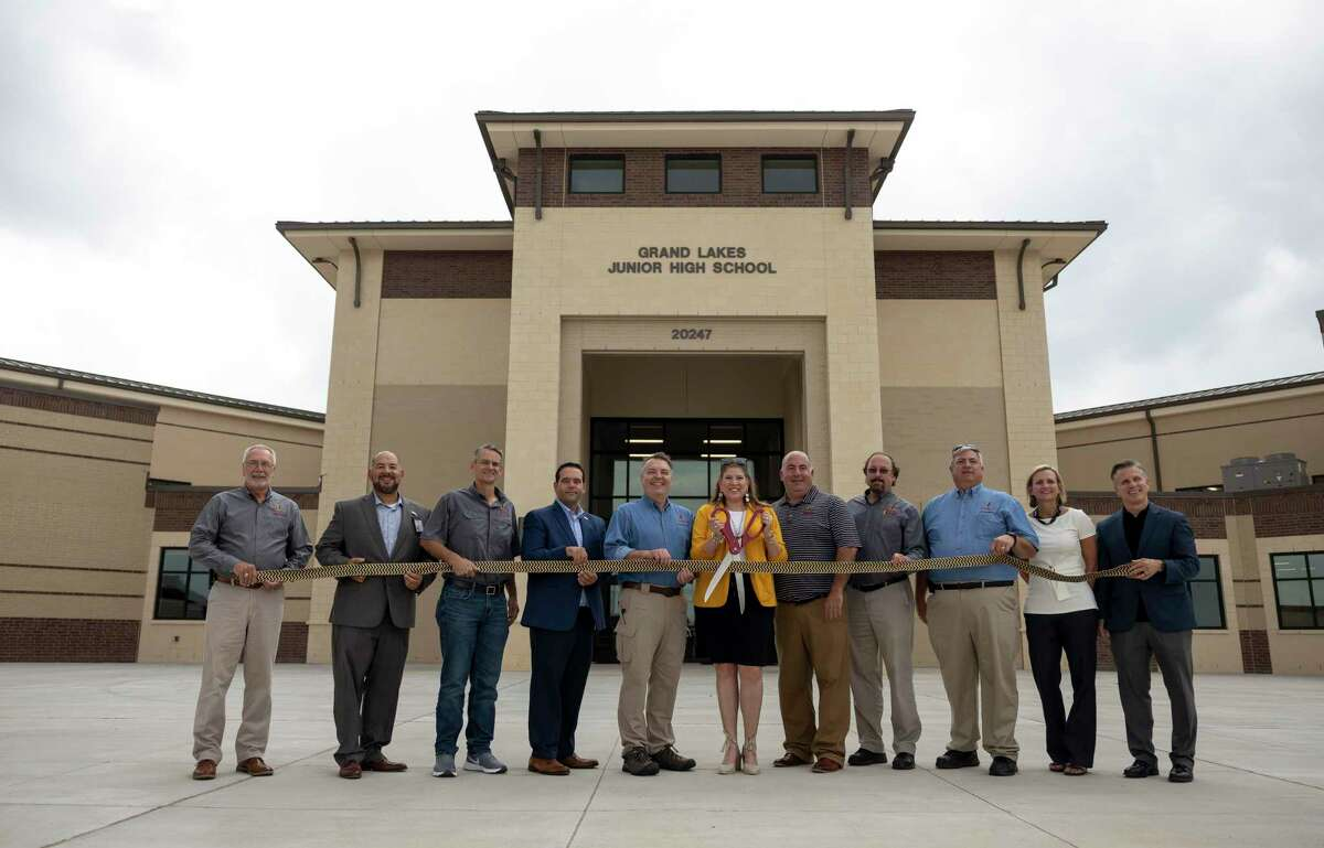 Administrators, staff and school board members pose for a portrait in front of at Grand Lakes Junior High during a ribbon cutting ceremony, Friday, Aug. 6, 2021, in Tomball.