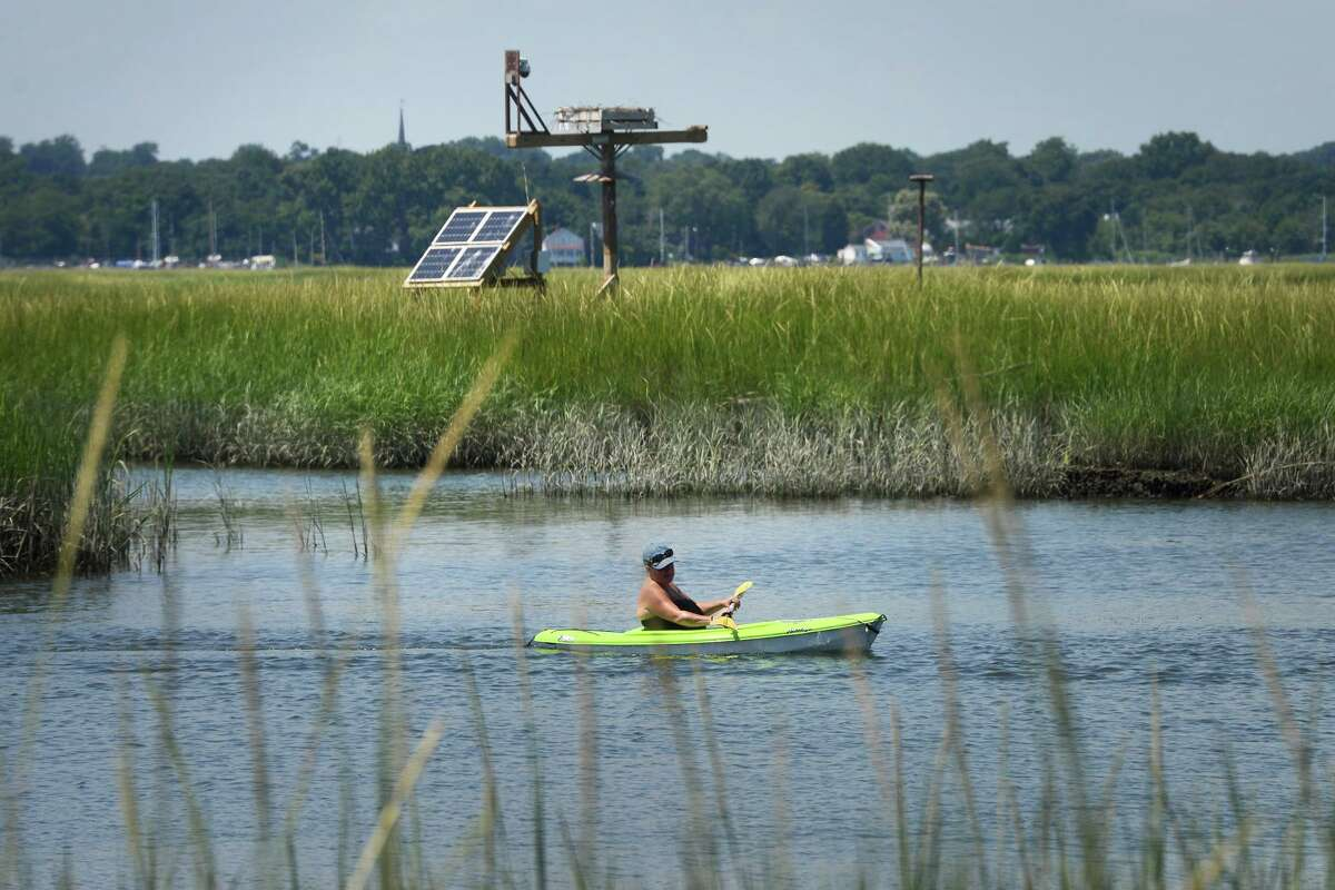 """With the popular osprey nest platform and """"osprey-cam"""" visible in the distance, a kayaker paddles through the marsh behind the Connecticut Audubon Society Coastal Center at Milford Point, in Milford, Conn. Aug. 6, 2021."""