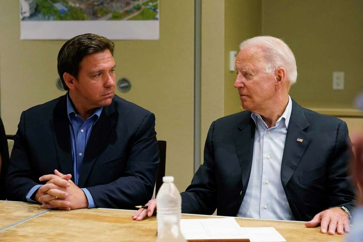 In this July 1, 2021, photo President Joe Biden, right, looks at Florida Gov. Ron DeSantis, left, during a briefing with first responders and local officials in Miami on the condo tower that collapsed in Surfside, Fla.