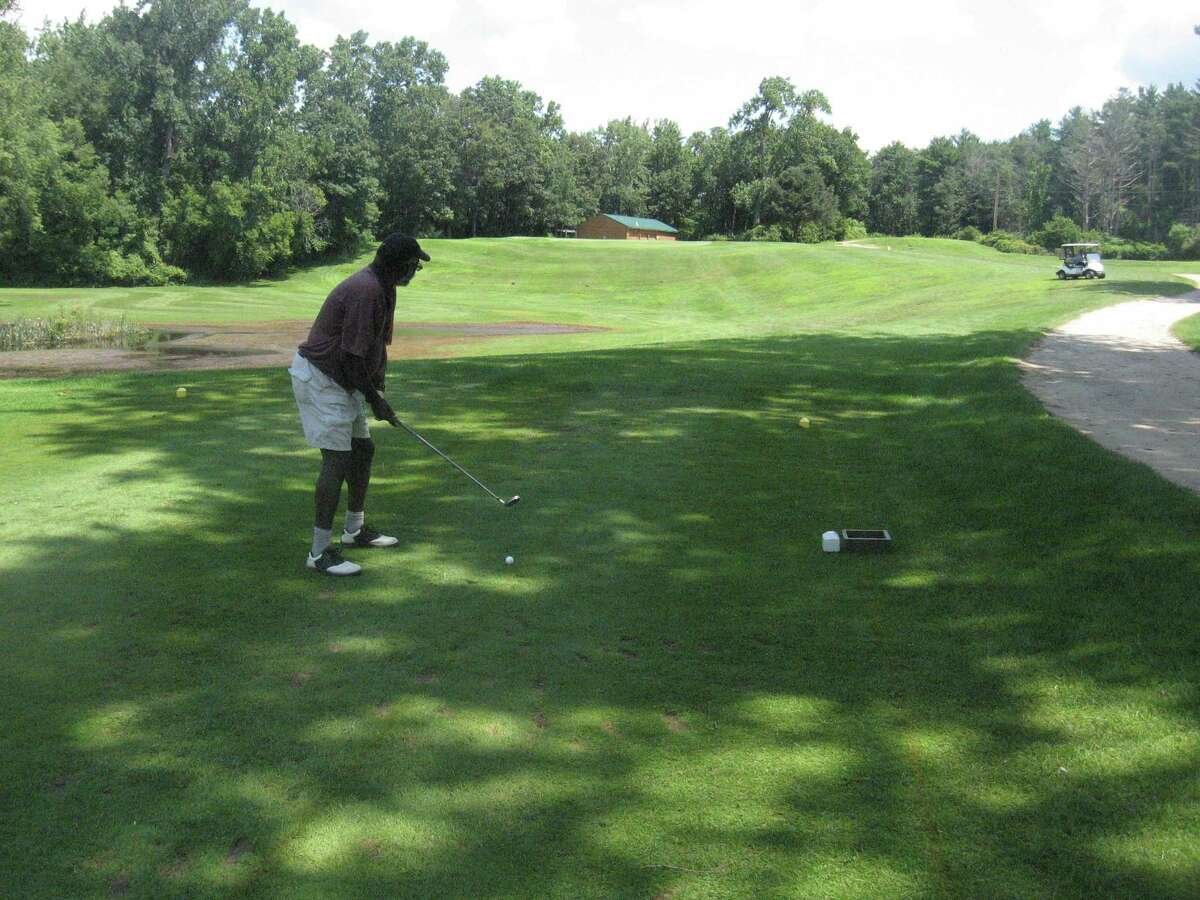 A golfer eyes a play while playing at the Canaan Country Club.