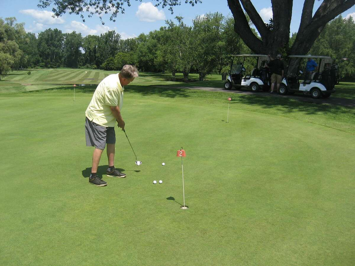 A golfer plays on the green at the Canaan Country Club.