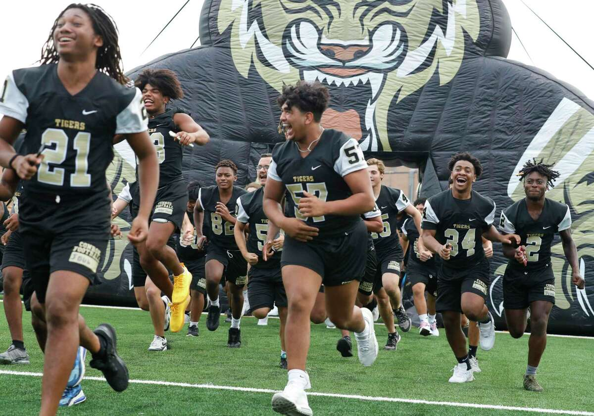 Jose Singh, center, takes the field with teammates during Meet the Tigers at Moorhead Stadium, Friday, Aug. 6, 2021, in Conroe. Community members saw performances by the Conroe High School's band, Golden Girls, cheerleaders and stayed to watch the football team practice under the lights.