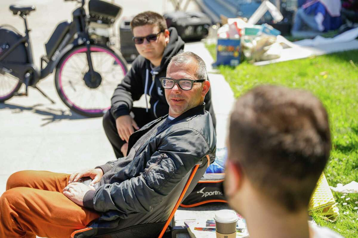Gary McCoy (center) chats with Ewan Barker Plummer (left) and Daniel Vainish as he stages a hunger strike outside San Francisco City Hall.