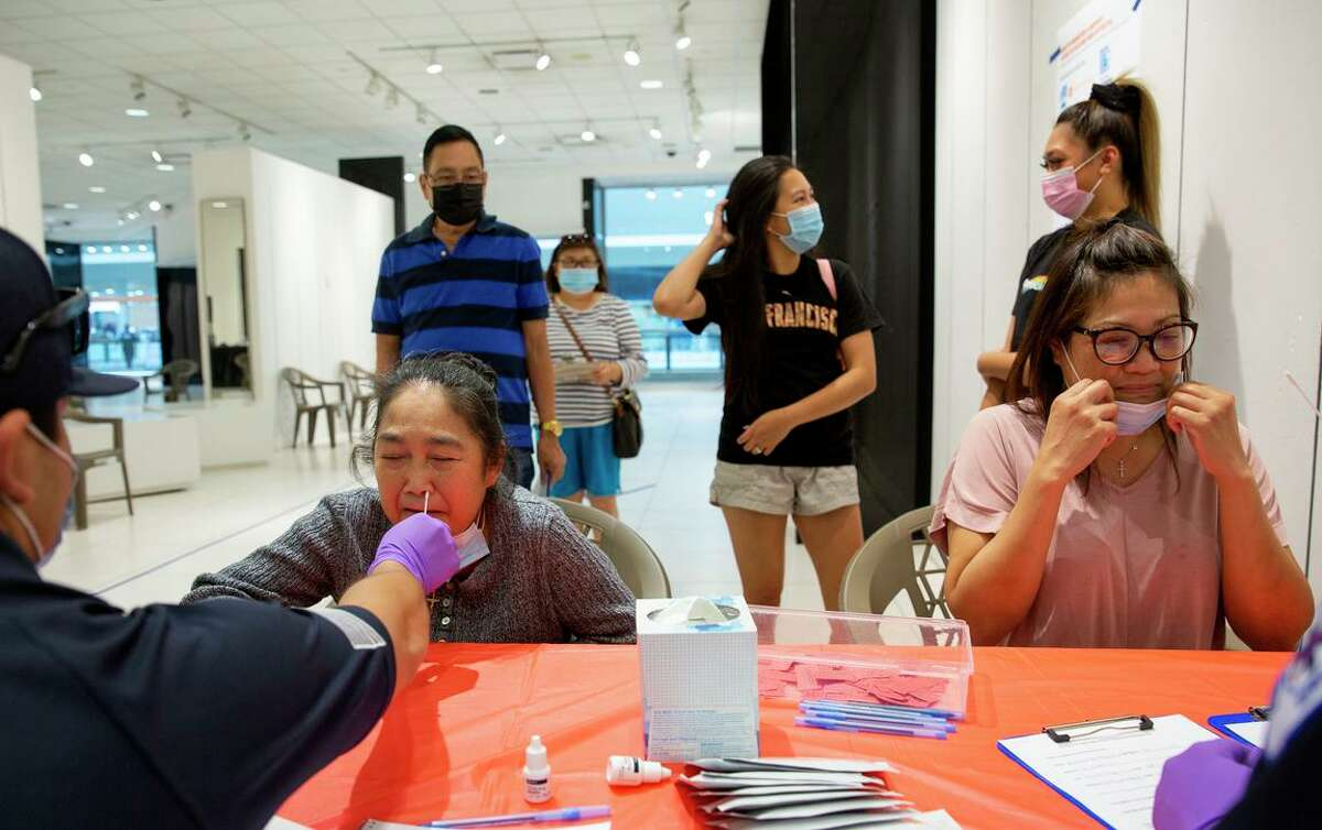 Cristina Arcilla (left) and her daughter Marizza Bautista-Ong take a coronavirus rapid test along with the rest of their family at a vaccination site at the Solano Town Center mall in Fairfield.
